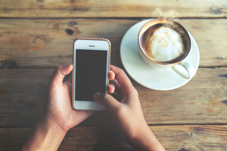 Close up of beautiful young hipster woman\'s hands holding mobile smart phone with hot coffee cup at cafe shop, female using cell telephone with blank copy space screen for your advertising text message. vintage color tone