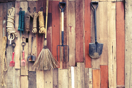 agricultural tools hang on wooden wall in farm - rural vintage style