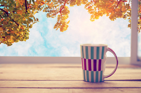 Photo pour Hot coffee cup on wood table in fall season. autumn tree background with blue sky. vintage color tone - image libre de droit
