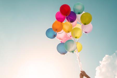 Foto de Hands of girl holding multicolored balloons done with a retro vintage filter effect, concept of happy birthday in summer and wedding honeymoon party (Vintage color tone) - Imagen libre de derechos