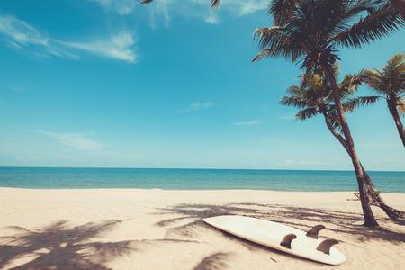 Foto de Surfboard on tropical beach in summer. landscape of summer beach and palm tree with sea, blue sky background. Vintage color tone - Imagen libre de derechos
