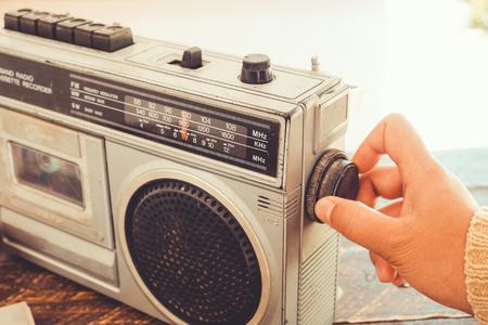 Foto de Retro lifestyle - Woman's hand switched and adjusting button cassette player and recorder for listen music - vintage color tone effect. - Imagen libre de derechos