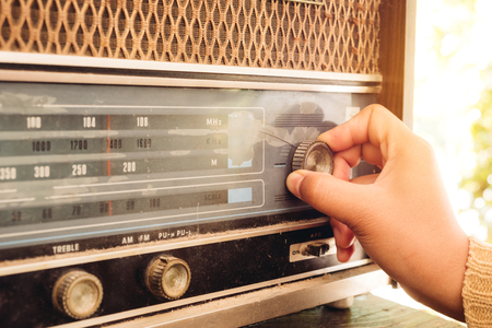 Foto de Retro lifestyle - Woman hand adjusting the button vintage radio receiver for listen music or news - vintage color tone effect. - Imagen libre de derechos