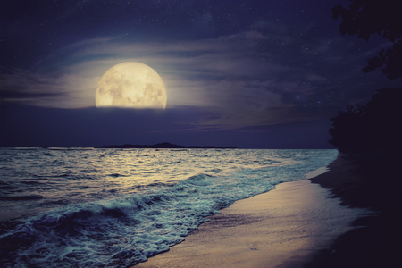 Beautiful fantasy tropical sea beach. Full moon (super moon) with cloud over seascape in night skies. Serenity nature background at nighttime. vintage and retro color filter style.