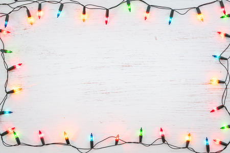 Foto de Christmas lights bulb frame decoration on white wood. Merry Christmas and New Year holiday background. top view - Imagen libre de derechos