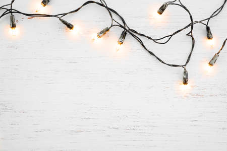 Foto de Christmas lights bulb decoration on white wood. Merry Christmas and New Year holiday background. top view - Imagen libre de derechos
