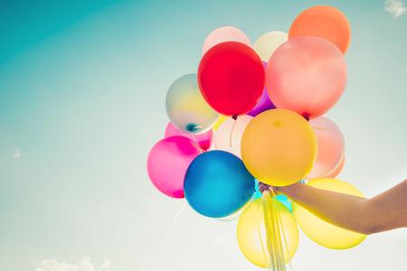 Foto de Girl hand holding multicolor balloons done with a retro filter effect, concept of happy birth day in summer and wedding honeymoon party, Vintage color tone style - Imagen libre de derechos