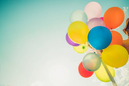Photo pour Girl hand holding multicolor balloons done with a retro photo filter effect, concept of happy birth day in summer and wedding honeymoon party, Vintage color tone style - image libre de droit