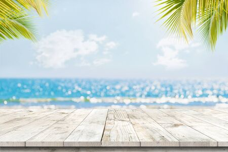 Foto de Top of wood table with seascape and palm leaves, blur bokeh light of calm sea and sky at tropical beach background. Empty ready for your product display montage.  summer vacation background concept. - Imagen libre de derechos