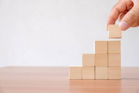 Foto de Business concept of ladder career path and growth success process. Hands of men arranging wood cube block stacking for top staircase shape on wooden table. - Imagen libre de derechos