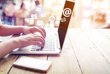 Photo pour Hand of female using laptop computer sending e-mail message with email address symbol and envelope icon. Online marketing concept. - image libre de droit