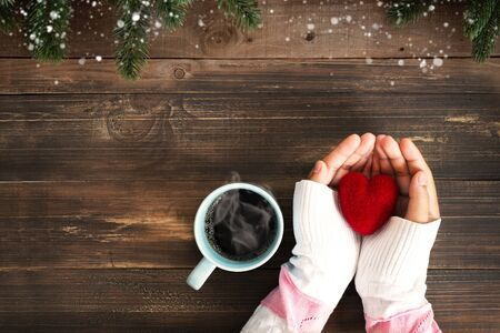 Photo pour Above view of woman hand holding red heart with hot cup of coffee on wood table. Christmas holiday and winter season - image libre de droit
