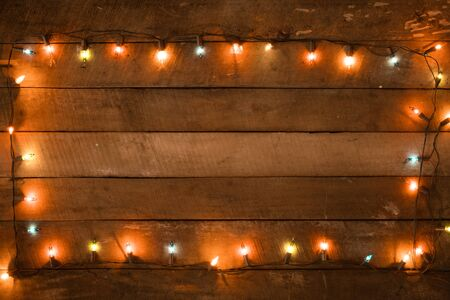 Foto de Christmas lights bulb decoration on old wood plank, frame border design. Merry Christmas and New Year holiday background. vintage color tone. - Imagen libre de derechos