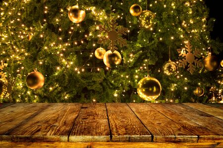 Foto de Beautiful Christmas tree backdrop and lights with top of empty wood table. ready for your product display or montage. Concept of background in Christmas and New year holidays. - Imagen libre de derechos