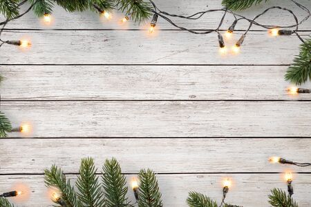Foto de Christmas lights bulb and pine leaves decoration on white wood plank, frame border design. Merry Christmas and New Year holiday background. top view. - Imagen libre de derechos