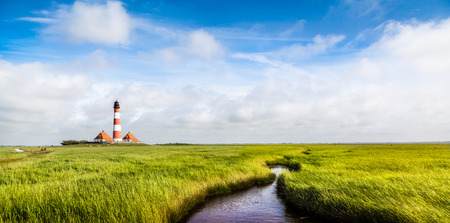 Beautiful landscape with small pond and lighthouse  at North Sea in Nordfriesland, Schleswig-Holstein, Germany