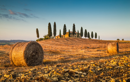 Beautiful Tuscany landscape with traditional farm house and hay bales in golden evening light, Val d Orcia, Italy