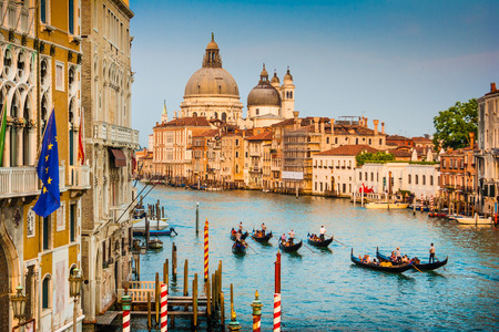 Beautiful view of Gondolas on famous Canal Grande with Basilica di Santa Maria della Salute at sunset in Venice, Italy