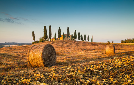 Beautiful Tuscany landscape with traditional farm house and hay bales in golden evening light, Val d Orcia, Tuscany, Italy