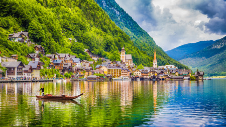 Photo for Scenic picture-postcard view of famous Hallstatt mountain village with Lake Hallstatt and traditional Pltte boat in the Austrian Alps, region of Salzkammergut, Austria - Royalty Free Image