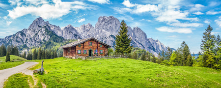 Foto de Panoramic view of scenic mountain landscape in the Alps with traditional mountain chalet and fresh green meadows in spring - Imagen libre de derechos