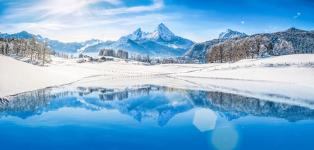 Foto de Panoramic view of beautiful white winter wonderland scenery in the Alps with snowy mountain summits reflecting in crystal clear mountain lake on a cold sunny day with blue sky and clouds - Imagen libre de derechos