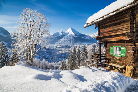 Photo pour Winter wonderland mountain scenery in the Alps with traditional mountain chalet on a cold sunny day with blue sky and clouds - image libre de droit
