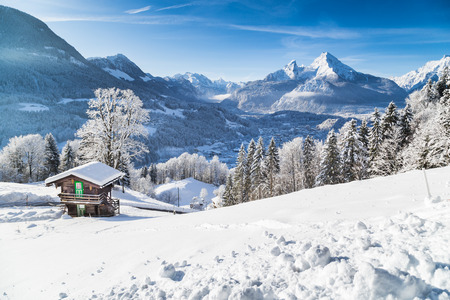 Winter wonderland mountain scenery in the Alps with traditional mountain chalet on a cold sunny day with blue sky and clouds