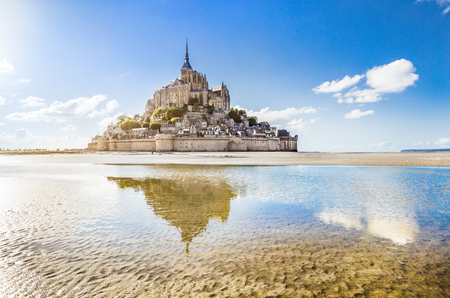 Panoramic view of famous Le Mont Saint-Michel tidal island on a sunny day with blue sky and clouds, Normandy, northern France
