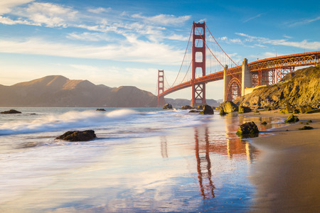 Foto de Classic panoramic view of famous Golden Gate Bridge seen from scenic Baker Beach in beautiful golden evening light on a sunny day with blue sky and clouds in summer, San Francisco, California, USA - Imagen libre de derechos