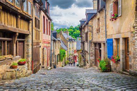 Beautiful view of scenic narrow alley with historic traditional houses and cobbled street in an old town in Europe with blue sky and clouds in summer with retro vintage  grunge filter effect