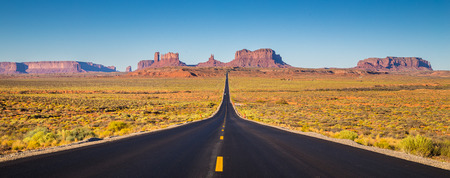 Photo pour Classic panorama view of historic U.S. Route 163 running through famous Monument Valley in beautiful golden evening light at sunset on a beautiful sunny day with blue sky in summer, Utah, USA - image libre de droit