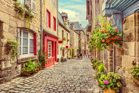 Photo pour Beautiful view of scenic narrow alley with historic traditional houses and cobbled street in an old town in Europe with blue sky and clouds in summer with retro vintage  grunge filter effect - image libre de droit