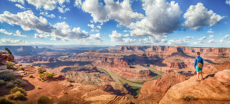 Panoramic view of young hiker standing on a cliff in in scenic Dead Horse Point State Park enjoying the view on a beautiful sunny day with blue sky and dramatic clouds in summer, Utah, USA