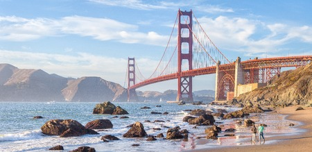 Photo pour Panoramic view of famous Golden Gate Bridge seen from Baker Beach in beautiful golden evening light at sunset with blue sky and clouds in summer, San Francisco, California, USA - image libre de droit