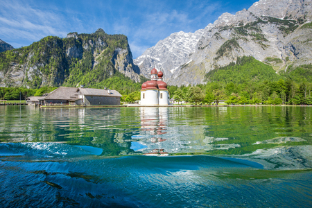 Photo for Classic panoramic view of Lake Konigssee with world famous Sankt Bartholomae pilgrimage church and Watzmann mountain on a beautiful sunny day in summer, Berchtesgadener Land, Bavaria, Germany - Royalty Free Image