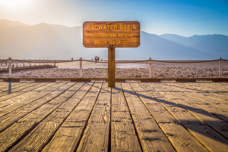 Wooden sign at famous Badwater Basin, the lowest point in North America with a depth of 282 ft (86 m) below sea level, at sunset, Death Valley National Park, California, USA