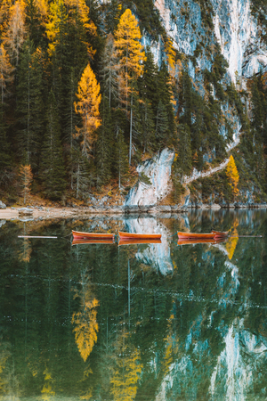 Photo pour Beautiful panoramic view of traditional wooden rowing boats and historic chapel reflecting in scenic Lago di Braies in the Dolomites, South Tyrol, Italy - image libre de droit