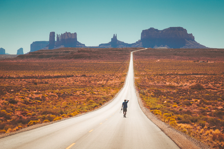 Photo pour Classic panorama view of young man walking on famous Forrest Gump Road in Monument Valley at noon, Utah, American West, USA - image libre de droit