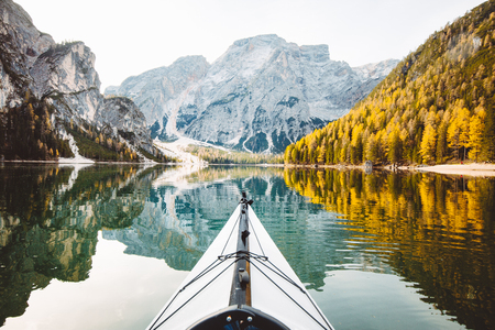 Foto per Beautiful view of kayak on a calm lake with amazing reflections of mountain peaks and trees with yellow autumn foliage in fall, Lago di Braies, Italy - Immagine Royalty Free
