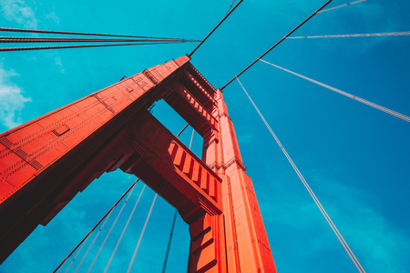 Foto per Beautiful low angle view of famous Golden Gate Bridge with blue sky and clouds on a sunny day in summer with retro vintage post - Immagine Royalty Free