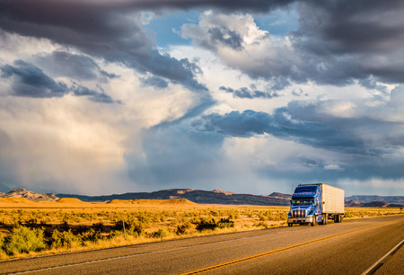 Photo pour Beautiful panorama view of classic semi trailer truck on empty highway with dramatic sky in golden evening light at sunset - image libre de droit