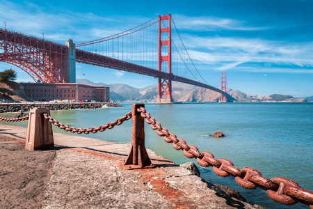 Foto de Classic view of famous Golden Gate Bridge with Fort Point National Historic Site on a beautiful sunny day with blue sky and clouds, San Francisco, USA - Imagen libre de derechos