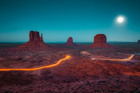Classic panoramic view of scenic Monument Valley with the famous Mittens and Merrick Butte with light trails at night in summer, Arizona, American Southwest, USA