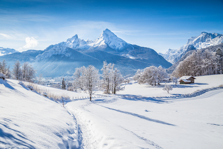 Photo pour Beautiful winter scenery with trees and mountain tops in the Alps on a sunny day with blue sky and clouds - image libre de droit