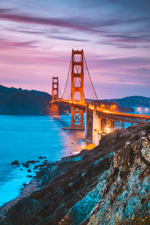 Photo for Classic panorama view of famous Golden Gate Bridge seen from scenic Baker Beach in beautiful post sunset twilight with blue sky and clouds at dusk in summer, San Francisco, California, USA - Royalty Free Image