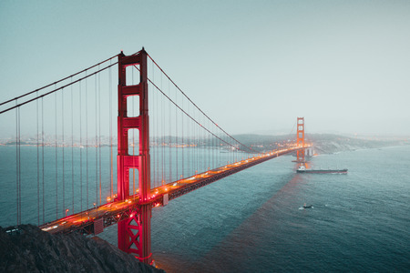 Photo for Classic panoramic view of famous Golden Gate with cargo freight ship in beautiful post sunset twilight during blue hour at dusk in summer, San Francisco, California, USA - Royalty Free Image