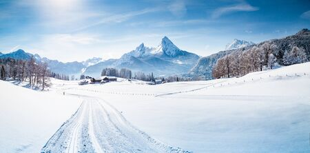 Scenic winter wonderland mountain scenery in the Alps with cross-country skiing track on a cold sunny day with blue sky and clouds
