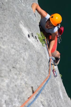 Photo pour Summer climbing. Young woman climbing a limestone rock - image libre de droit