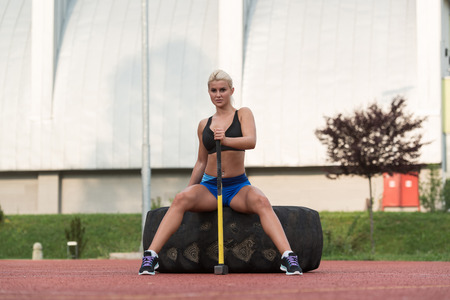Portrait Of A Physically Fit Young Woman With Hammer And Tire Resting After Exercise